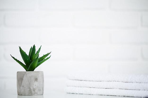 Asciugamani bianchi sulla tavola bianca con lo spazio della copia sul fondo della stanza da bagno.