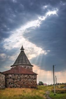 La torre bianca del monastero di solovetsky sotto nuvole blu e un lucernario con raggi di sole