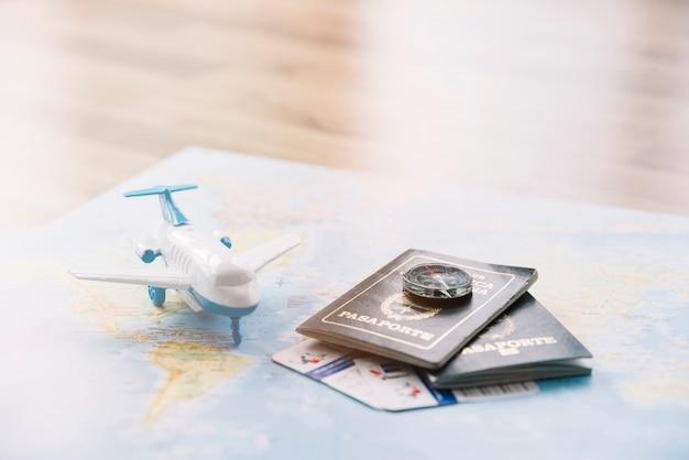 Aeroplano giocattolo bianco; bussola su passaporti e carta di franchigia bagaglio sulla mappa contro il tavolo di legno