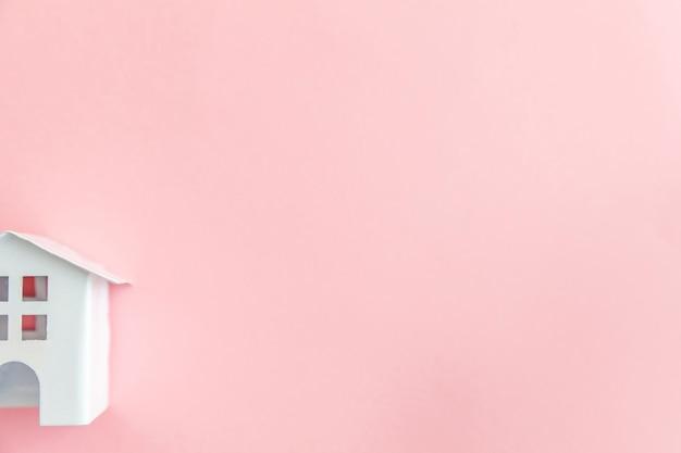 Casa giocattolo bianca isolata su sfondo rosa pastello. concetto di casa dei sogni di assicurazione sulla proprietà ipotecaria