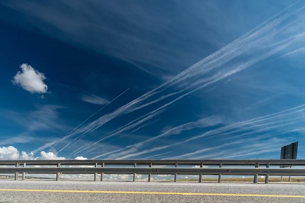 Tracce bianche di condensa di vapore acqueo dagli aerei sopra l'autostrada