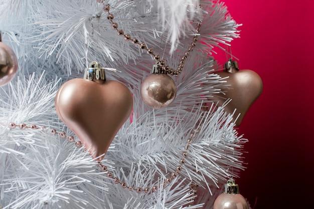 Albero bianco decorato con giocattoli decorativi, cuore e perline su uno sfondo bordeaux. spazio vuoto per il testo. celebrazione dell'inverno, capodanno, natale. primo piano dell'albero di natale.