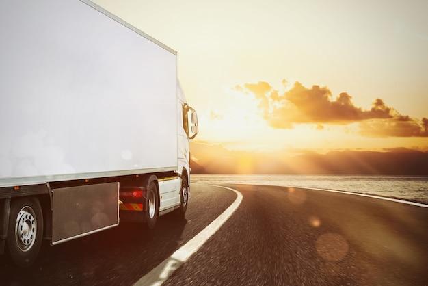 Camion bianco che si muove sulla strada in un paesaggio naturale al tramonto