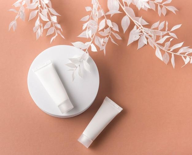 Tubetti di crema bianchi su fondo marrone e ramo decorativo con foglie bianche