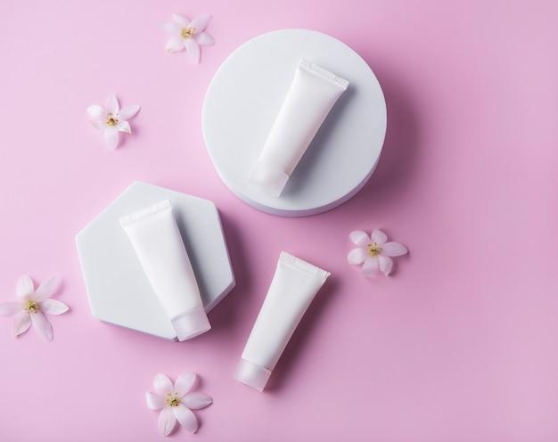Tubetti bianchi di crema su una parete rosa e fiori decorativi