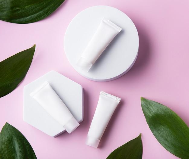 Tubetti bianchi di crema su una parete rosa con foglie verdi