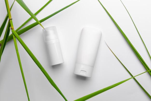 Tubi bianchi con crema viso e corpo su sfondo bianco con foglie verdi