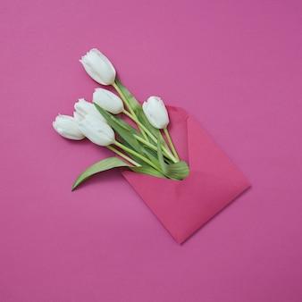 Bouquet di tulipani bianchi in busta artigianale su uno sfondo magenta con spazio di copia. cartolina postale per congratulazioni. lay piatto.