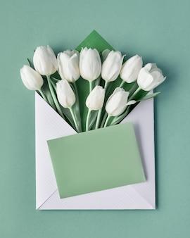 Tulipani bianchi in busta di carta con adesivo decorativo cuore su sfondo verde chiaro menta