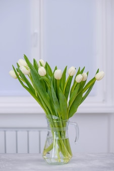 Tulipani bianchi sul tavolo in camera con copia spazio