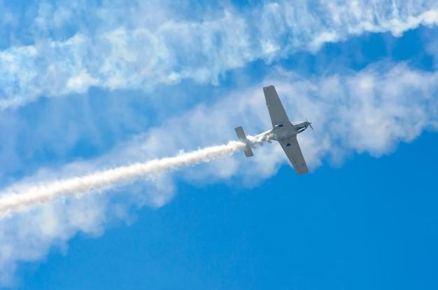 Aereo turboelica bianco con una traccia di fumo bianco contro un cielo blu.