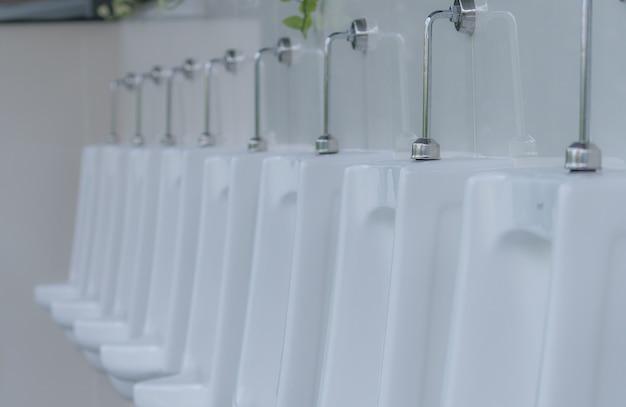 Orinatoi bianchi nel bagno pubblico degli uomini orinatoi in ceramica in fila nel bagno degli uomini salute della vescica dell'uomo
