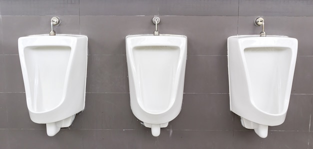 Orinatoi bianchi nella toilette degli uomini