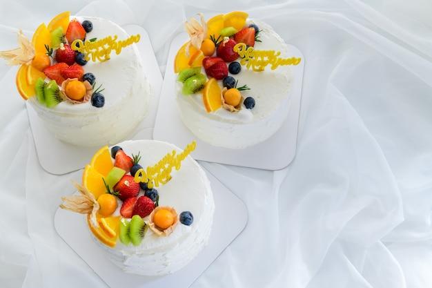 Torta alla vaniglia bianca con felice anno nuovo e condita con arancia