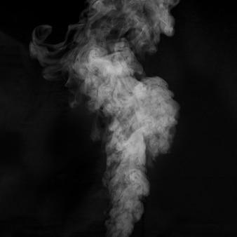 Vapore bianco spray vapore dal saturatore d'aria. frammenti di fumo su sfondo nero. sfondo astratto, elemento di design, da sovrapporre alle immagini