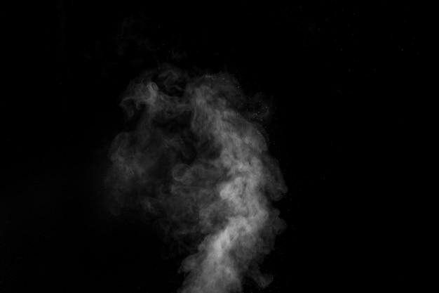 Vapore bianco spruzzato dal saturatore d'aria. frammenti di fumo su una parete nera.