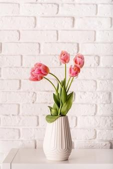 Vaso bianco con bouquet di bellissimi tulipani sul fondo del muro di mattoni
