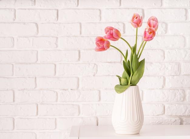 Vaso bianco con bouquet di tulipani rosa sul fondo del muro di mattoni con lo spazio della copia