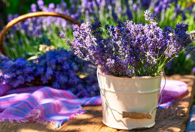 Vaso bianco con bouquet di lavanda sulla tavola di legno, sul fondo del campo di lavanda
