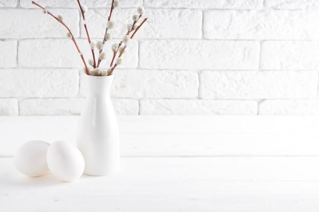 Vaso bianco con ramo di salice, uovo bianco e tazze su un tavolo bianco copia spazio concetto di pasqua
