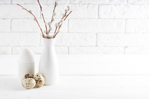 Vaso bianco con ramo di salice, uovo bianco, uova di quaglia e tazze su un tavolo bianco copia spazio concetto di pasqua