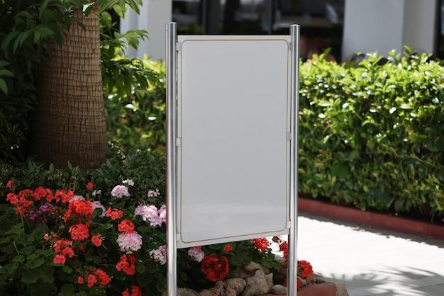 Il cartellone pubblicitario verticale bianco si trova nel mezzo del giardino
