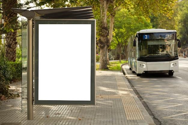 Tabellone per le affissioni verticale bianco, con il bus sulla via della città