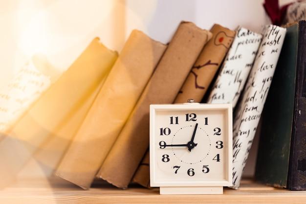 Orologio vintage bianco e pila di libri, primo piano