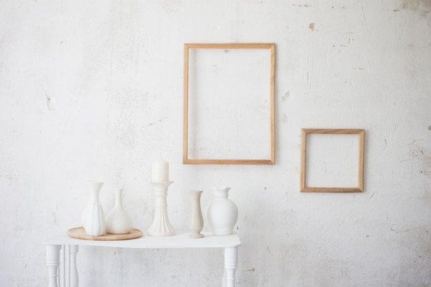 Interno vecchio vintage bianco con vasi e cornici