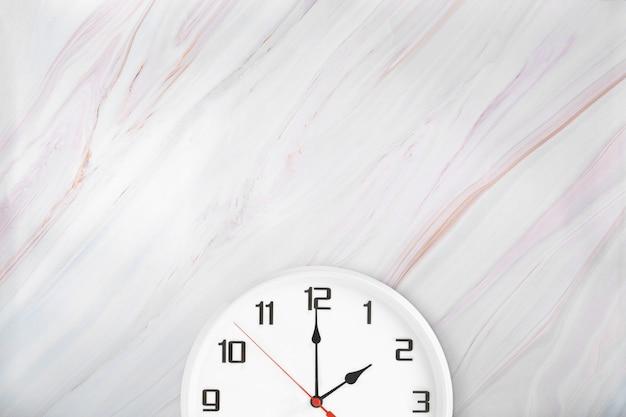 Orologio da parete bianco su sfondo di marmo naturale