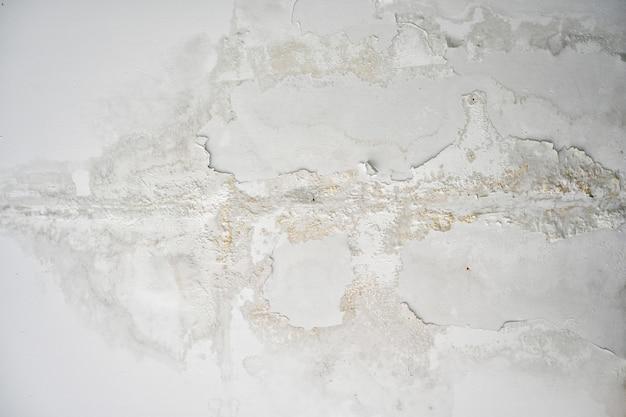 Frammento di muro bianco con graffi e crepe, grunge texture