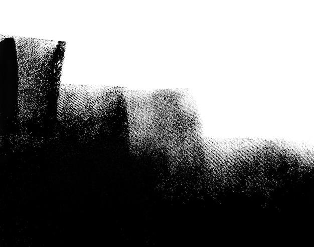 Muro bianco parzialmente dipinto di nero con un rullo di vernice.