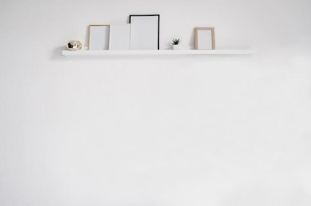 Parete bianca con cornici. sfondo per testo, design e pubblicità. posto per foto.