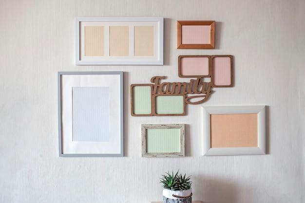 Muro bianco con set di diverse cornici vuote verticali e orizzontali per creare una galleria di foto di famiglia sul muro, per catturare un momento, modello di mockup sul muro bianco, stile di vita
