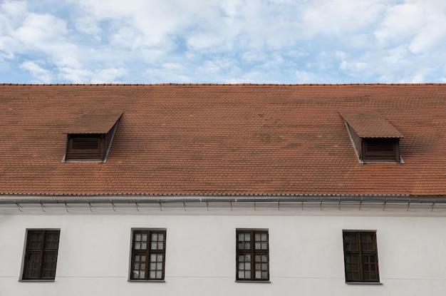Muro bianco, finestre in legno, tetto a scandole