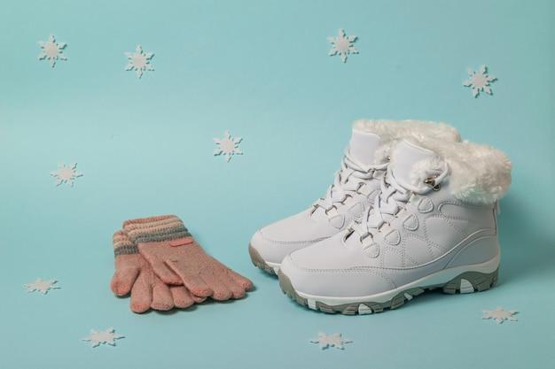 Scarpe da ginnastica bianche calde e guanti lavorati a maglia su uno sfondo blu con fiocchi di neve. scarpe sportive per l'inverno.