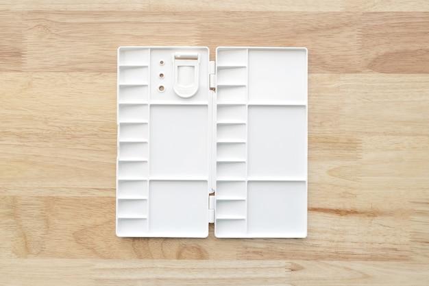 Tavolozza acquerello bianco. vassoio vuoto dell'acquerello isolato su fondo di legno. tavolozza di vernice di plastica bianca.