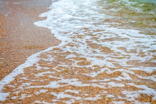 Onda bianca sulla spiaggia sabbiosa gialla vuota estate o clima tropicale sfondo natura sfondo