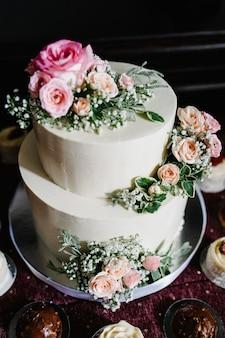 Torta nuziale bianca con fiori rosa e verdi su un tavolo festivo con pasticceria