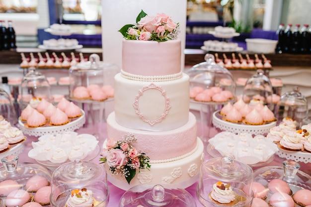 Torta nuziale bianca con fiori rosa e verdure su un tavolo festivo con dolci e sfondo sfocato.