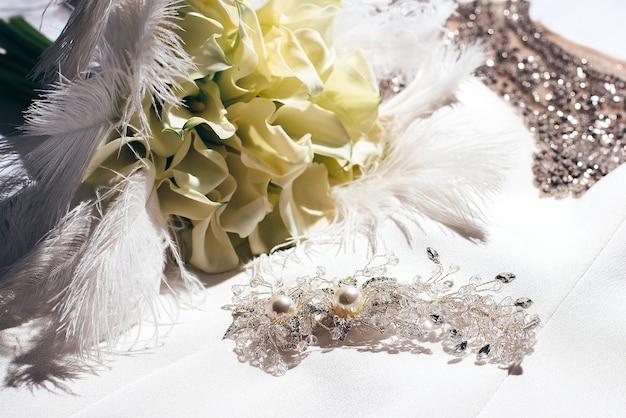 Abito da sposa bianco decorato con perline dorate giace accanto a un mazzo di fiori gialli e piume e fermagli per capelli dorati