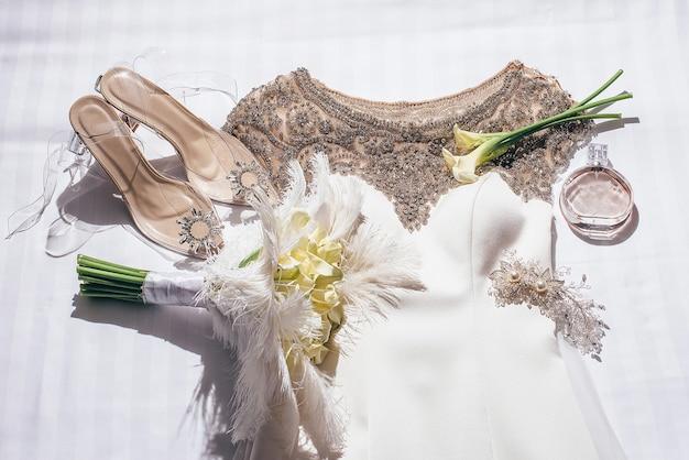Abito da sposa bianco decorato con perline dorate giace accanto alle scarpe della sposa decorate con pietre accanto a un mazzo di fiori gialli e piume e forcine per capelli in colore dorato e profumo chanel