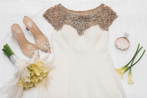 Abito da sposa bianco decorato con perline dorate giace accanto alle scarpe della sposa decorate con pietre accanto a fiori gialli e profumo chanel