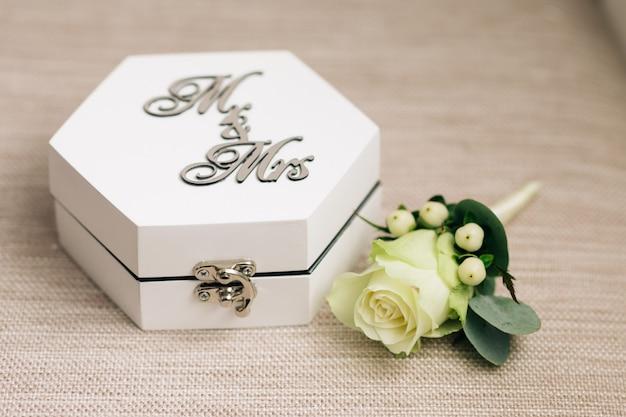 Primo piano bianco del fiore e della scatola dell'anello di cerimonia nuziale