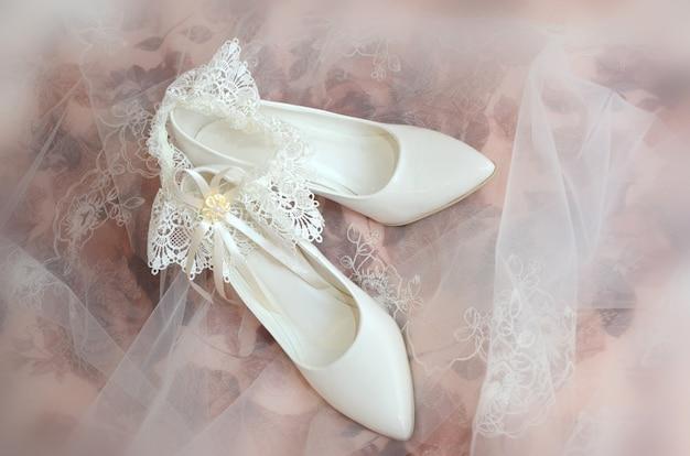Scarpe da sposa bianche e giarrettiera della sposa sotto un velo delicato su uno sfondo sfocato