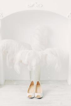 Scarpe da sposa bianche sopra il camino e piume di struzzo in interni bianchi