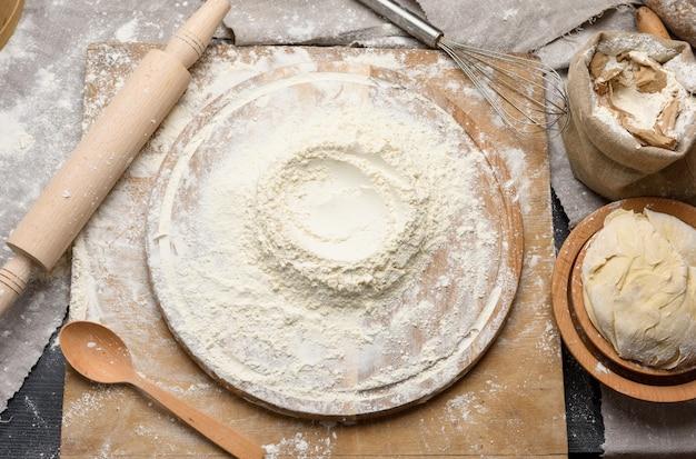 Farina di frumento bianco ammucchiata su una tavola di legno rotonda, impasto con un piatto di legno, vista dall'alto