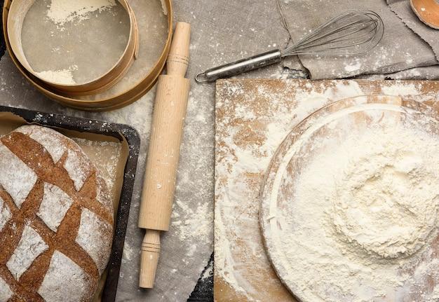 Farina di frumento bianco ammucchiata su una tavola di legno rotonda, vista dall'alto