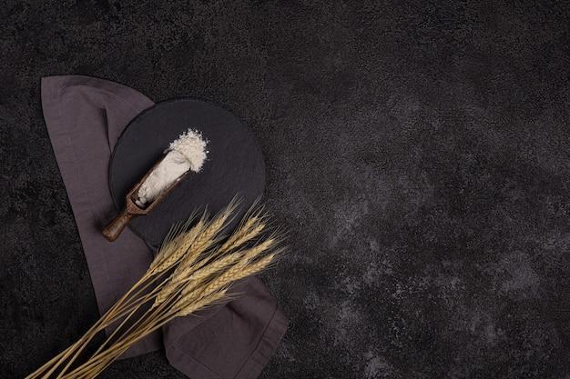 Farina di frumento bianca in un cucchiaio di legno su uno sfondo strutturale scuro su un piatto di pietra nera