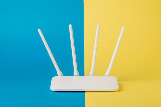 Router wi-fi bianco su una superficie gialla e blu